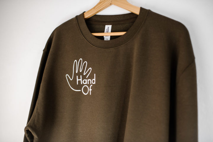 Hand Of jumper in olive green (logo detail)